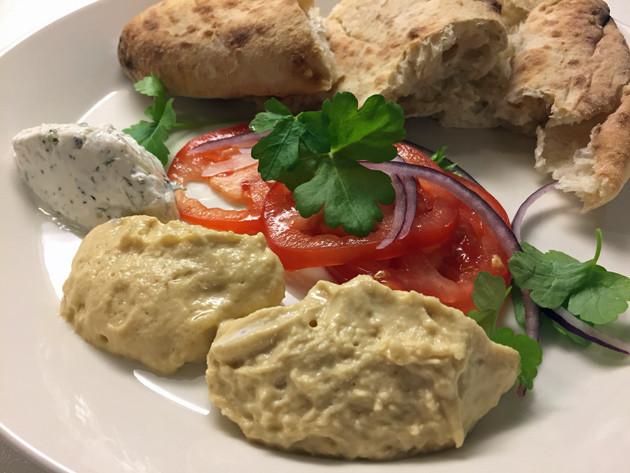 hummus, tsatsiki ja leipää lautasella