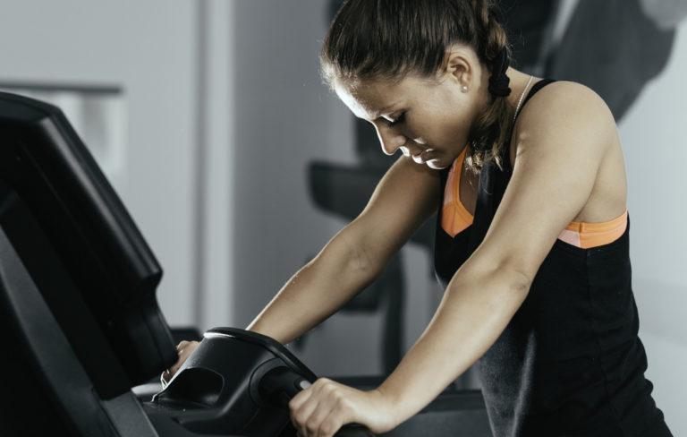 Sykevälivaihtelu: nainen nojaa juoksumattoon salilla.