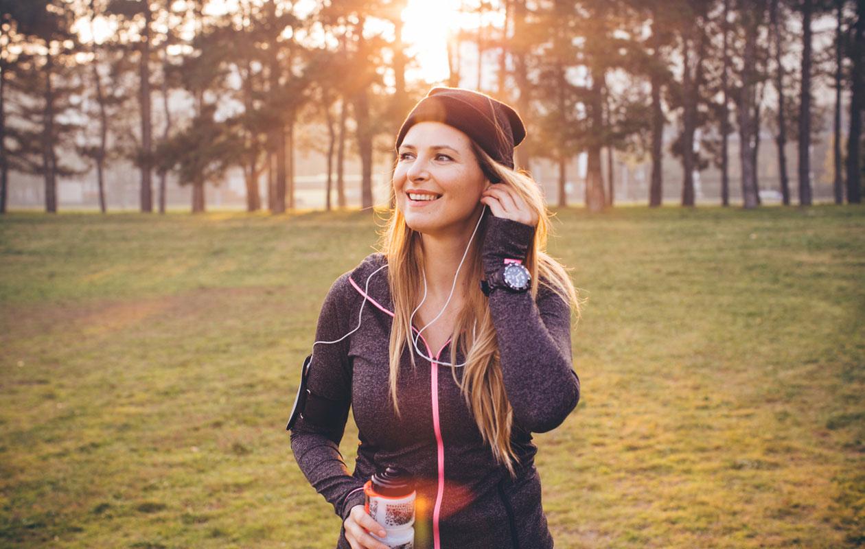 Juoksukoulu: nainen seisoo ulkona aurinkoisella säällä.